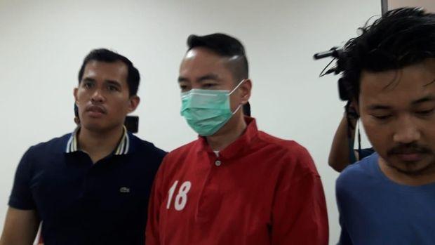 Andy Wibowo mengenakan masker dan baju tahanan.