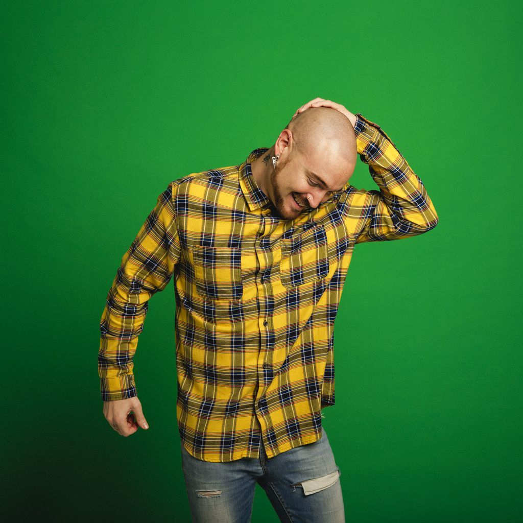 Mid adult hipster man dancing infront of a green studio background.