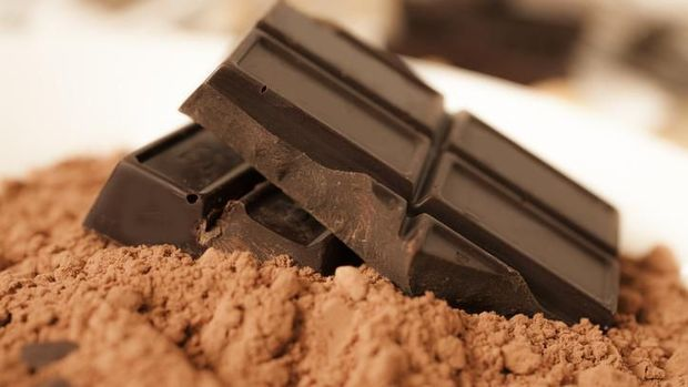 Stack of dark chocolate bars with cocoa powder used for baking lies on top of a kitchen counter ready to be chopped and melted into a dessert.  Food preparation. No people.