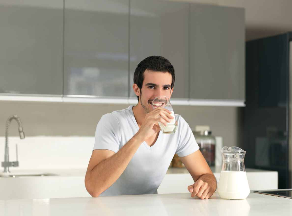 Latin man drinking milk and looking at the camera