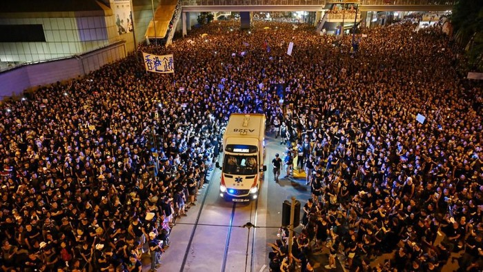 An ambulance is pictured surrounded by thousands of protesters dressed in black during a new rally against a controversial extradition law proposal in Hong Kong on June 16, 2019. - Hundreds of thousands of protesters choked Hong Kongs streets for a second straight on June 16 in a defiant rebuke of a reviled extradition law, piling pressure on the citys embattled pro-Beijing leader despite a weekend climbdown. (Photo by HECTOR RETAMAL / AFP)