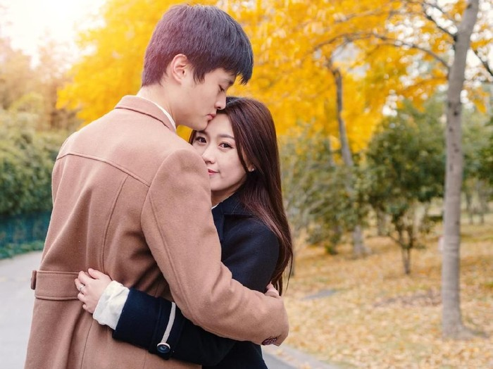 Chinese young man and woman hug and stand together with emotional expression, lover concept.