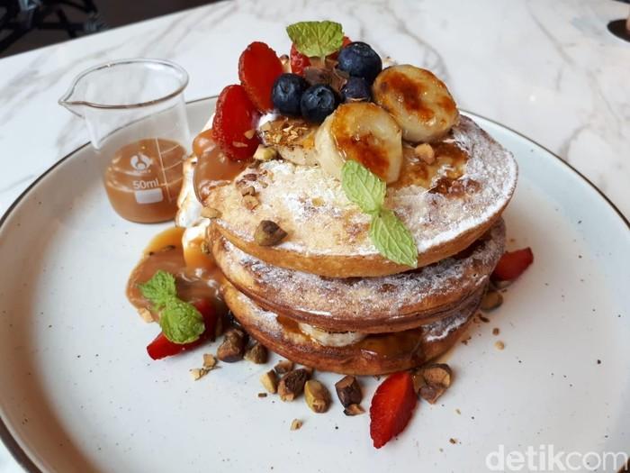Pancake enak juga bisa dicicip di Tobys Estate. Coffee shop ini menawarkan Tobys Signature Pancake dari kategori All Day Brunch. Tiga lembar pancake disusun dengan taburan gula halus. Di atasnya diberi fruit compote yang terdiri dari pisang, blueberry dan strawberry. Foto: dok. detikFood