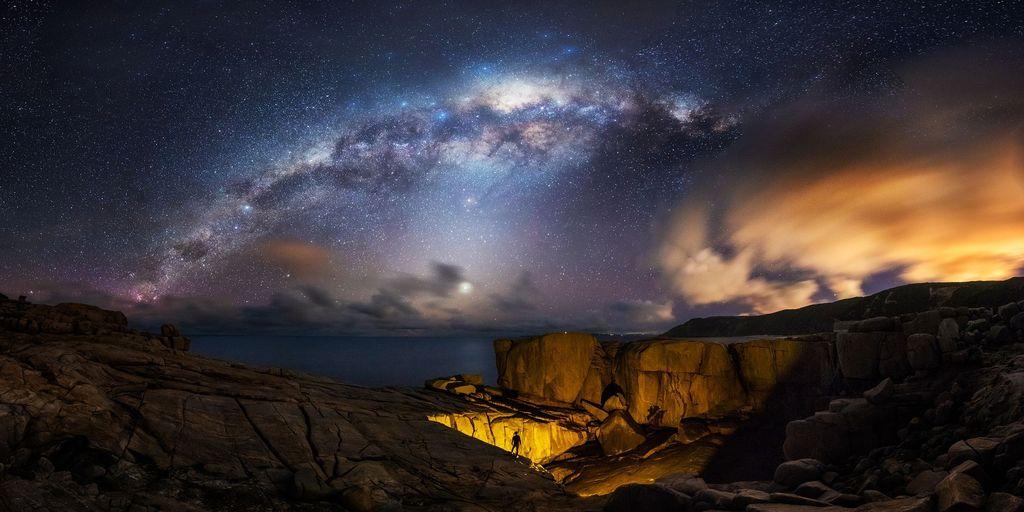 Setiap tahun sekitar bulan September dan Oktober, fenomena alam Bima Sakti berada pada posisi terbaiknya. Inti galaksi berada tepat di tengah-tengah langit. Fotografer berdiri di tebing dekat laut dan dengan obornya ia menyalakan jembatan alami, yang tampak seperti lubang raksasa. (Foto: Astronomy Photographer 2019)