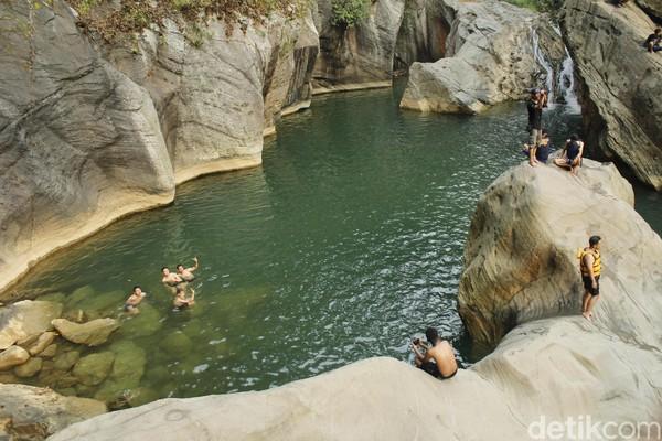 Di bebatuan ini, traveler yang punya adrenalin berlebih bisa melompat dari atas batu yang membentuk ceruk ke kolam. Berani? (Yudha Maulana/detikcom)