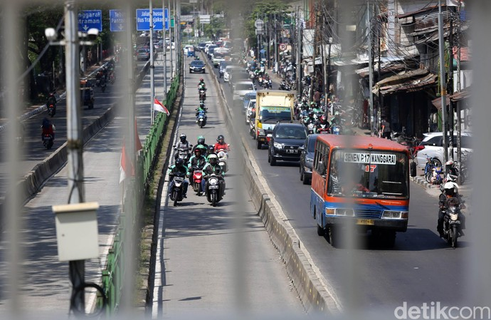 Sejumlah pengendara motor nekat menerobos jalur TransJakarta di Jalan Sultan Agung, Jakarta Selatan, Selasa (18/6/2019).