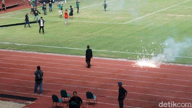Massa suporter juga melempar petasan ke dalam stadion