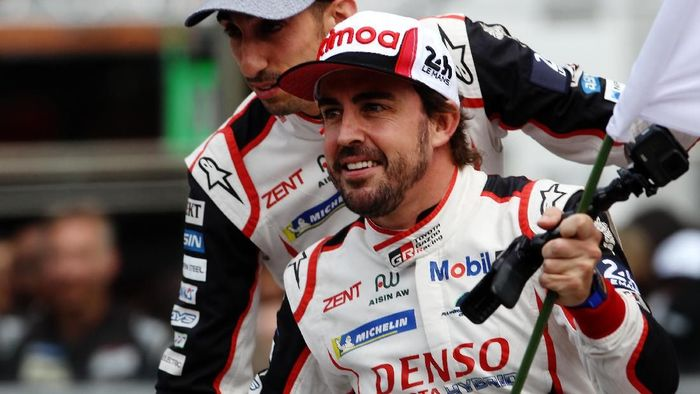 LE MANS, FRANCE - JUNE 16:  Fernando Alonso celebrates as he and co-drivers Kazuki Nakajima and Sebastien Buemi take the flag in their Toyota Gazoo Racing TS050 Hybrid to secure the win during the Le Mans 24 Hour Race at the Circuit de la Sarthe on June 16, 2019 in Le Mans, France. (Photo by Ker Robertson/Getty Images)