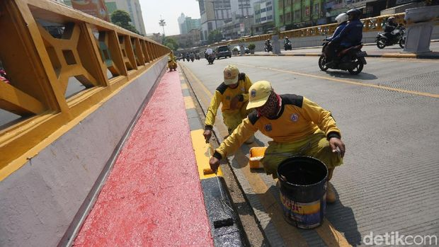 Sejumlah petugas Bina Marga mengecat marka jalan di kawasan Underpass Tanah Abang. Hal itu dilakukan untuk menyambut HUT Jakarta ke-492.
