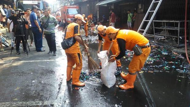 Petugas membersihkan sampah sisa kebakaran di lokasi.