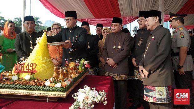 Gubernur DKI Anies Baswedan saat memotong tumpeng perayaan HUT DKI di Monas.