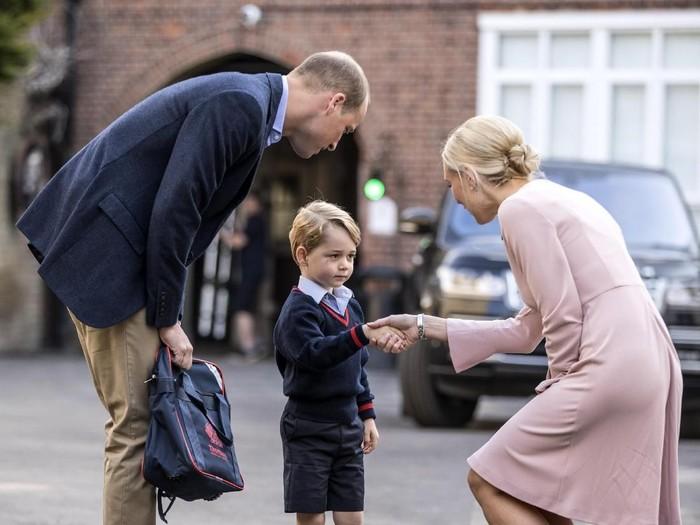 Ditemani Pangeran William, Pangeran George bersalaman dengan guru saat hari pertamanya sekolah di Thomass Clapham, London, Inggris, pada 2017 lalu.  (Foto: Getty Images)