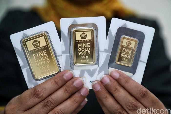 Seorang pegawai memperlihatkan emas logam mulia PT Aneka Tambang (Persero) Tbk atau Antam di salah satu Butik Emas Logam Mulia PT Antam, Jakarta, Senin (24/6).