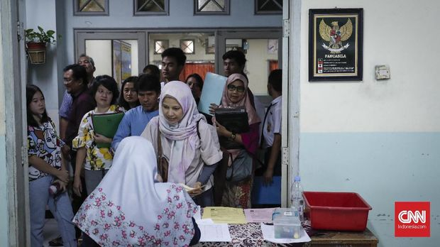 Orangtua siswa antre PPDB di SMAN 8 Jakarta, Senin (24/6).