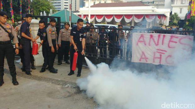 Petugas keamanan Balai Kota memadamkan api dengan APAR.