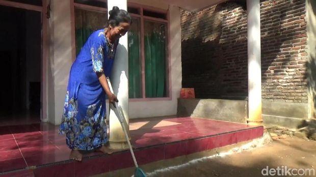 Warga membersihkan ulat bulu di depan rumahnya/