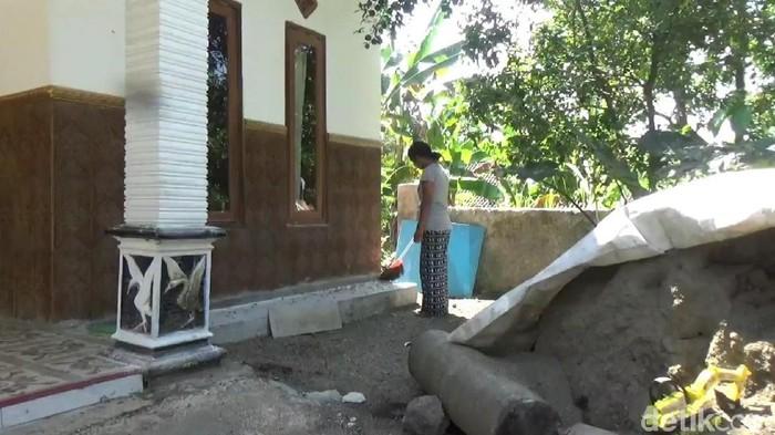 Warga membersihkan ulat di depan rumahnya/Foto: Muhajir Arifin
