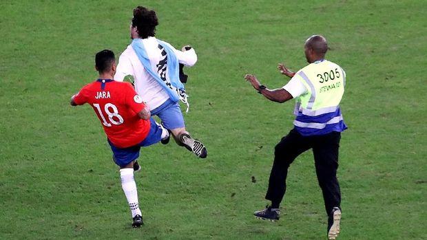 Gonzalo Jara (kiri) menendang fan penyusup di lapangan Stadion Maracana. (