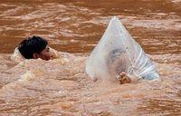 Seorang pria membawa siswa ke dalam kantong plastik sebrangi sungai ke sekolah