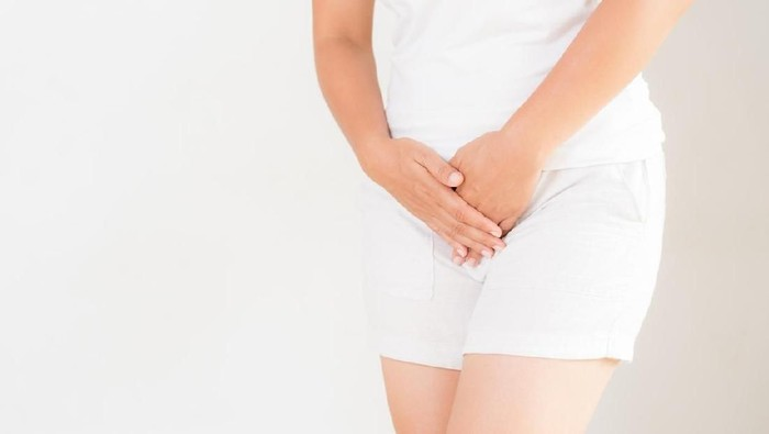Young woman in yellow short dress standing with her hands between legs, needs a restroom, isolated for white background. Womens health, gynecology.