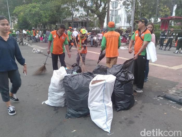 Pasukan oranye membersihkan lokasi aksi. (Arief/detikcom)