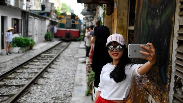 Ilustrasi -- Seorang wanita berfoto selfie dengan latar belakang kereta api yang sedang melaju di rel kawasan populer di Hanoi, Vietnam (Manan VATSYAYANA/AFP)