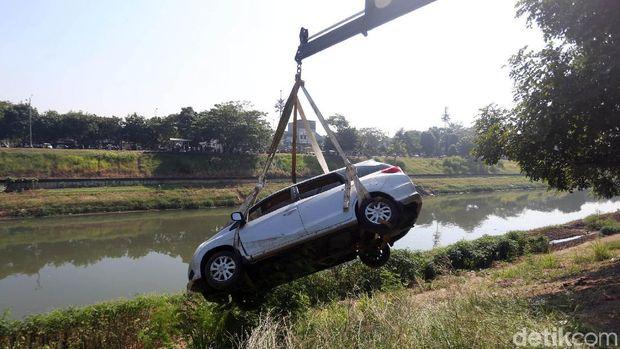 Sejumlah petugas mengevakuasi mobil yang terperosok ke Kanal Banjir Timur.