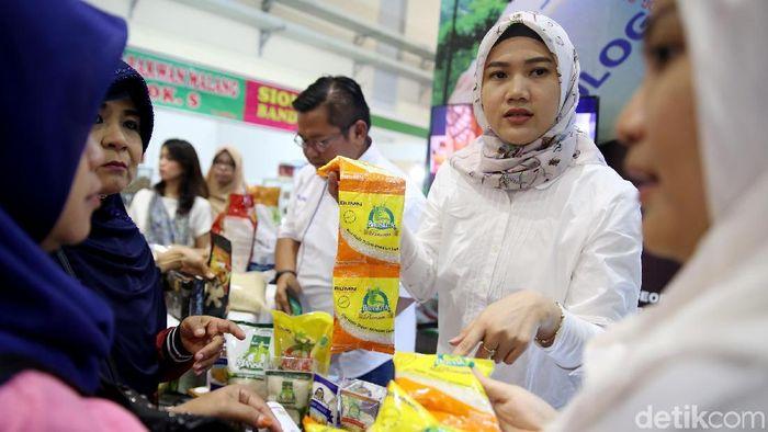 """Petugas BULOG melayani pembeli di stand Pameran Agrofood Expo 2019, Jakarta Convention Center (JCC), Jumat (28/6). Melalui brand """"KITA"""",  BULOG mengenalkan beragam produk makanan sehat (healthy food) dengan berbagai produk unggulan yang berkualitas dan sehat mulai dari beras, gula, minyak goreng, terigu, daging dan bakso."""