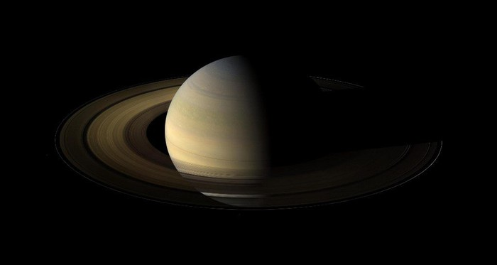 This NASA handout image obtained October 19, 2009 shows Saturn during an equinox captured by the robot explorer Cassini. The images comprising the mosaic, taken over about eight hours, were extensively processed before being joined together. With no enhancement, the rings would be essentially invisible in this mosaic. To improve their visibility, the dark right half of the rings has been brightened relative to the brighter left half by a factor of three, and then the whole ring system has been brightened by a factor of 20 relative to the planet. So the dark half of the rings is 60 times brighter, and the bright half 20 times brighter, than they would have appeared if the entire system, planet included, could have been captured in a single image.The images were taken on August 12, 2009, beginning about 1.25 days after exact equinox, using the red, green and blue spectral filters of the wide angle camera and were combined to create this natural color view. The images were obtained at a distance of approximately 526,000 miles from Saturn and at a Sun-Saturn-spacecraft, or phase, angle of 74 degrees. Image scale is 31 miles per pixel. AFP PHOTO/NASA/JPL/SPACE/RESTRICTED TO EDITORIAL USE (Photo by HO / NASA / AFP)