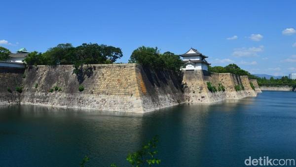 Begitu memasuki kawasan castle, pengunjung akan disambut pemandangan indah dinding raksasa yang dikelilingi danau buatan. Tumpukan bebatuan warna abu-ubu gelap dipadu birunya air di danau buatan, menjadi kombinasi menarik yang memanjakan mata. (Dana Aditiasari/detikcom)