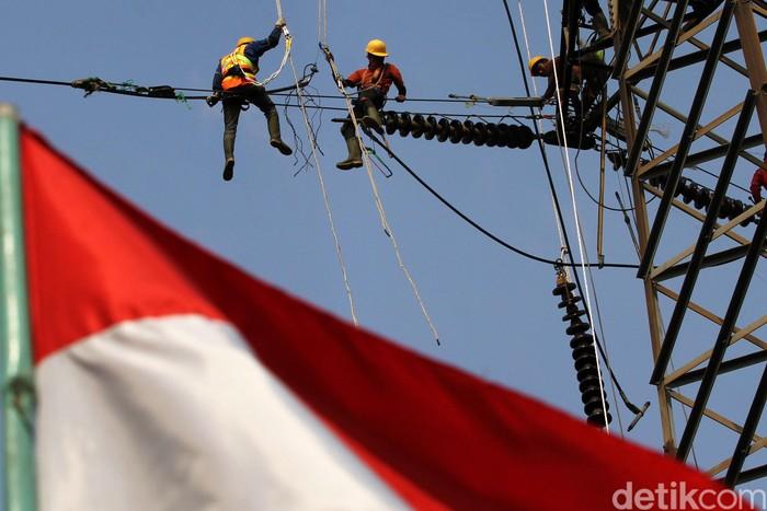Sejumlah petugas PLN tengah melakukan reconductoring tower listrik jalur Karet-Angke, Jakarta, Selasa (2/7). Mereka beraksi di ketinggian layaknya spiderman.