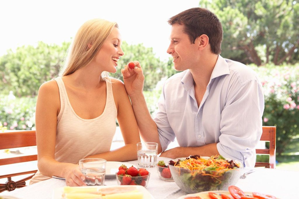 Happy loving couple enjoying breakfast in a cafe. Love, dating, food, lifestyle