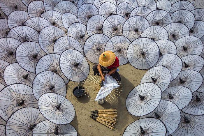 Payung tak hanya menjadi alat untuk melindungi tubuh dari hujan. Kerajinan payung hias juga menjadi salah satu buah tangan favorit bagi wisatawan. Seperti foto ini yang menampilkan seorang perajin tengah membuat kerajinan payung hias di Myanmar. Istimewa/Dok. Boredpanda/Agora Photo/@aungthuya.