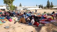Puluhan imigran yang selamat pun berkumpul di tengah lapangan untuk menyelamatkan diri dan membawa serta barang-barang mereka keluar dari pusat detensi migran yang telah rusak akibat serangan udara.