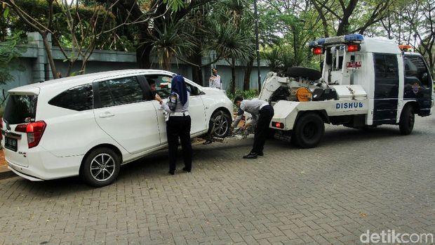 Belasan mobil diderek petugas dari Dinas Perhubungan di Kawasan Gambir dan Kemayoran, Jakarta Pusat, Kamis (4/7/2019).