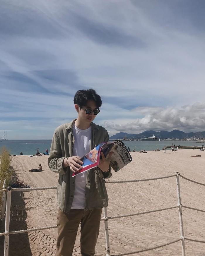 Melalui akun Instagram dntlrdl, Choi Woo Shik kerap mengunggah momen-momen seru untuk 431.000 followersnya. Termasuk membaca majalah di pinggir laut. Foto: Instagram dntlrdl
