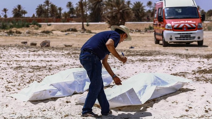 EDITORS NOTE: Graphic content / A representative of the Tunisian Red Crescent association checks bodies recovered from a boat carrying 86 migrants that capsized off the Tunisian coast while crossing the Mediterranean from Libya to Italy, as they lie on a beach in Aghir in Tunisias southern island of Djerba on July 6, 2019. - The latest tragedy came to light the same week as 44 migrants were killed in an air strike on their detention centre in a suburb of the Libyan capital. (Photo by ANIS MILI / AFP)