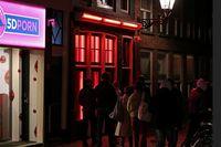 Etalase kaca dengan warna merah, tempat pekerja seks menjajakan diri (Reuters)