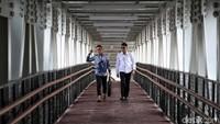 Sejumlah jurnalis melintas di atas skybridge di Stasiun LRT Velodrome, Jakarta Timur, Kamis (11/7).