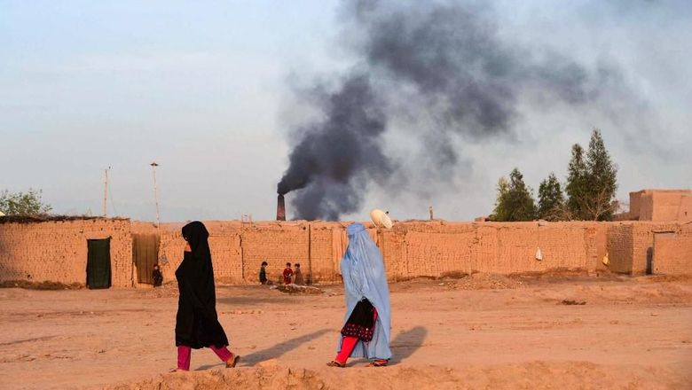 In this photograph taken on April 3, 2019, Afghan women walk near a brick factory as smoke rises up in the sky from a chimney on the outskirts of Jalalabad. (Photo by NOORULLAH SHIRZADA / AFP)