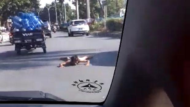 Selain naik kap mobil, pria diduga gila itu juga tidur di tengah jalan