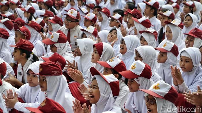 Ratusan siswa SD mengikuti upacara di Hari pertama sekolah di SDN 01 Rawa Badak Utara, Jakarta Utara. Mereka memakai seragam Merah Putih.
