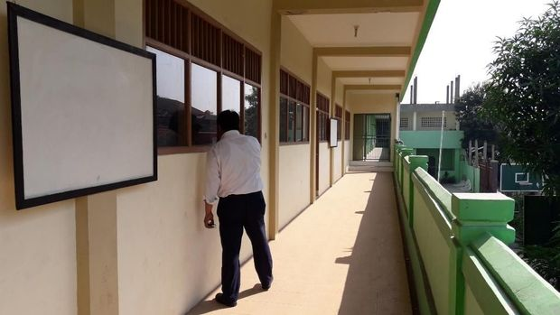 Guru mengintip ke sebuah kelas.