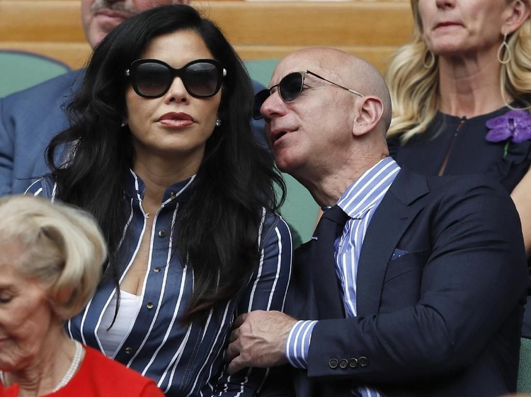 Amazon Founder and CEO Jeff Bezos, right, and Lauren Sanchez, watch Serbias Novak Djokovic play Switzerlands Roger Federer during the mens singles final match of the Wimbledon Tennis Championships in London, Sunday, July 14, 2019. (Adrian Dennis/Pool Photo via AP)
