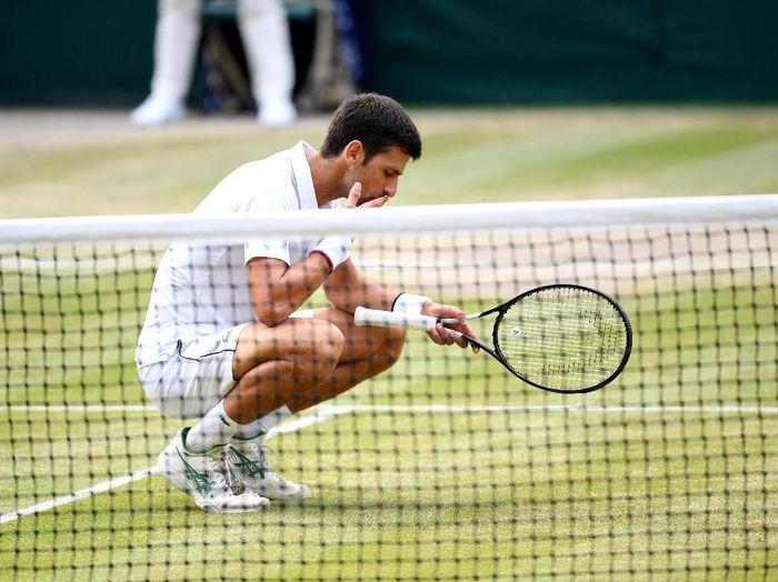 Novak Djokovic makan rumput usai memenangi duel dengan Roger Federer di final Wimbledon 2019 (Matthias Hangst/Getty Images)