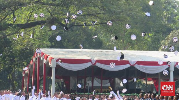 Para perwira melemparkan topi ke udara sebagai ungkapan kegembiraan kelulusannya dari akademi.