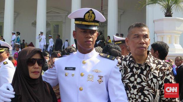 Letda M. Yudhie (tengah) bersama kedua orang tuanya usai pelantikan di Halaman Istana Merdeka, Jakarta, Selasa (16/7).