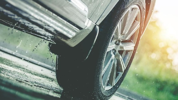 Car Driving in the Rain. Modern Rain Summer Season Tires on the Wet Pavement. Closeup Aquaplaning Photo.