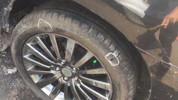 Lubang bekas peluru di dekat ban mobil.