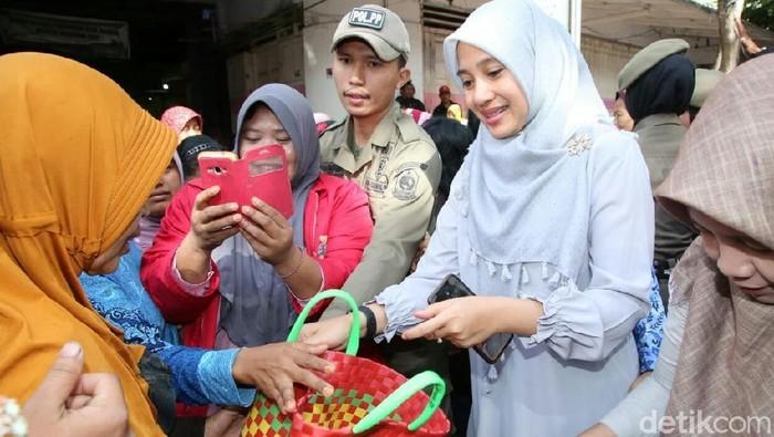 Dani Azwar Anas membagikan tas kepada ibu-ibu di pasar (Foto: Ardian Fanani)